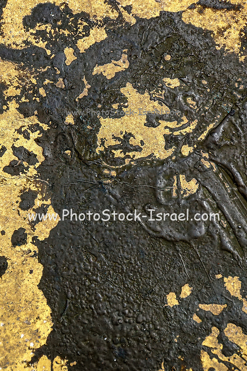 black tar smudges on a yellow wall. With a bit of imagination a head and face can be seen in the mess