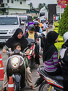 08 JULY 2013 - PATTANI, PATTANI, THAILAND:  Muslim women on motorcycles line up to get into a grocery store in Pattani, Thailand, Monday, the day before Ramadan. Ramadan starts July 9 and Monday was the last day observant Muslims were able to eat and drink during daylight hours. Muslims fast during the holy month of Ramadan, taking breakfast before dawn and not eating again until after sunset. The restaurants in Pattani, a Muslim majority city in southern Thailand, were packed Monday afternoon and evening.   PHOTO BY JACK KURTZ