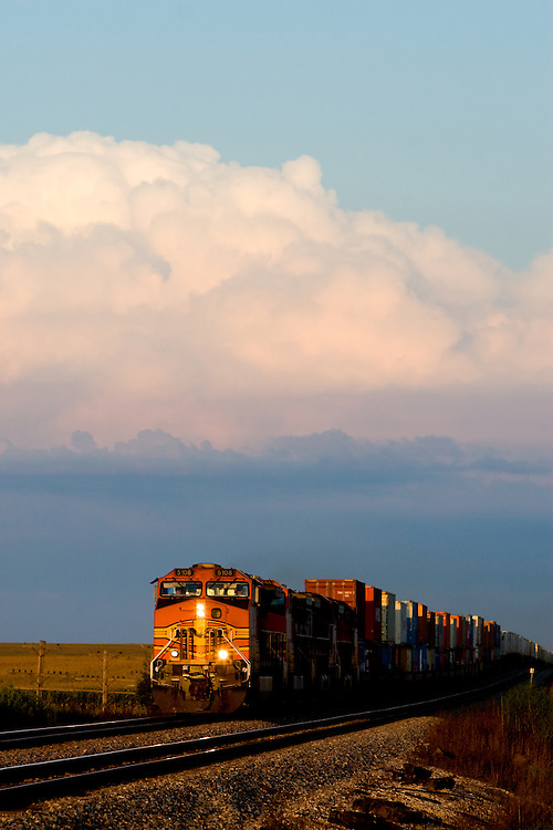 As thunderstorms loom on the horizon, a westbound BNSF intermodal train flies across the central Illinois prairie approaching Laura, IL.