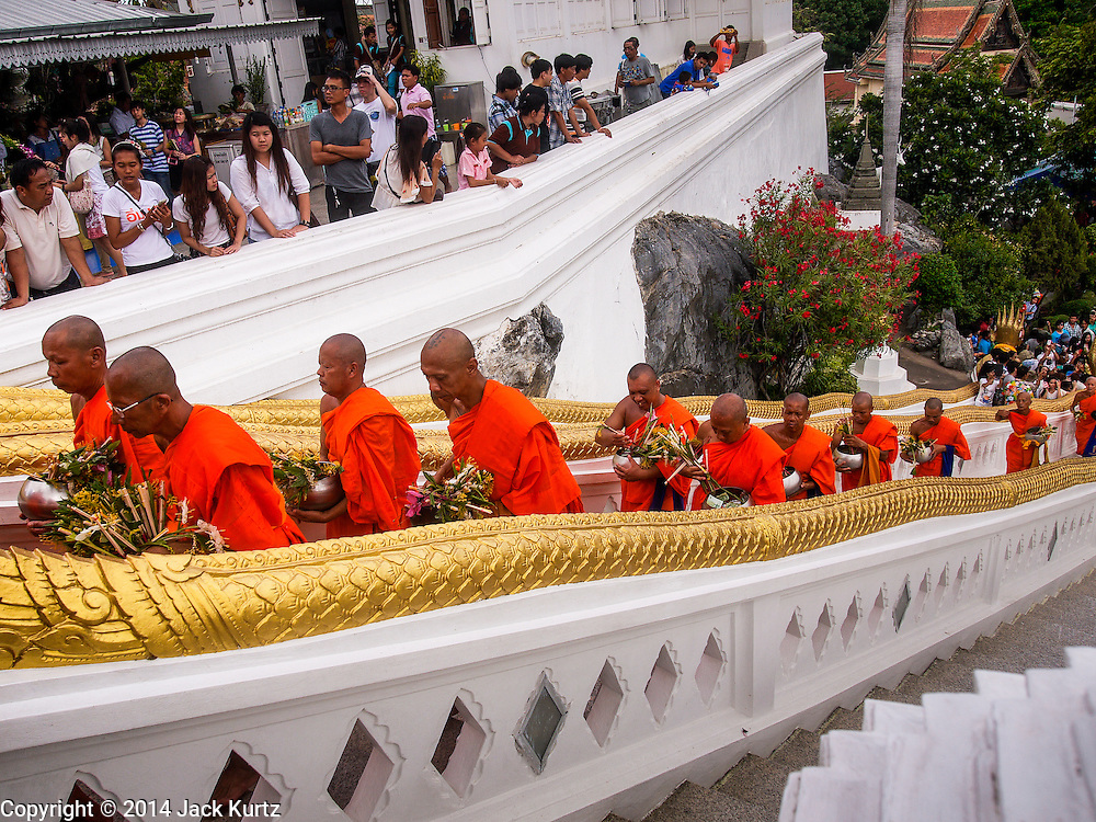 """12 JULY 2014 - PHRA PHUTTHABAT, SARABURI, THAILAND: Buddhist monks climb the stairs to Wat Phra Phuttabat during the Tak Bat Dok Mai in Saraburi province of Thailand. Wat Phra Phutthabat is famous for the way it marks the beginning of Vassa, the three-month annual retreat observed by Theravada monks and nuns. The temple is highly revered in Thailand because it houses a footstep of the Buddha. On the first day of Vassa (or Buddhist Lent) people come to the temple to """"make merit"""" and present the monks there with dancing lady ginger flowers, which only bloom in the weeks leading up Vassa. They also present monks with candles and wash their feet. During Vassa, monks and nuns remain inside monasteries and temple grounds, devoting their time to intensive meditation and study. Laypeople support the monks by bringing food, candles and other offerings to temples. Laypeople also often observe Vassa by giving up something, such as smoking or eating meat. For this reason, westerners sometimes call Vassa """"Buddhist Lent.""""    PHOTO BY JACK KURTZ"""