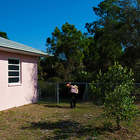 TAMPA, FL -- March 22, 2011 -- Shannon Moore, broker/owner of Green Lion Realty, walks around a vacant home for sale to look at stolen air conditioning unit in North Port, Fla., 2011.  A recent study showed that one and five homes in the state of Florida is vacant.