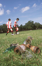 Two young boys playing football in park near rusty cans and broken glass,