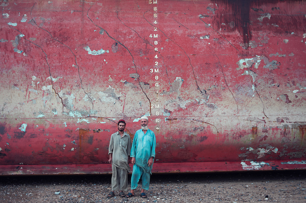 Security Guard Muhammad Haleen, 50 years with his son Muhammad Haleem, 25 years old at the Gadani ship breaking yard, Balochistan Province, Pakistan on August 16, 2011. Muhammad originates from Sawbi, Sarhad Province, Khyber Pakhtunya, 1500km to the north of the country. He has nine children. Muhammad earns 13,000 Pakistani rupees ($150 USD) a month. He lives in a makeshift shack built on the site where he works. He feels there is no respect for employees in his position.