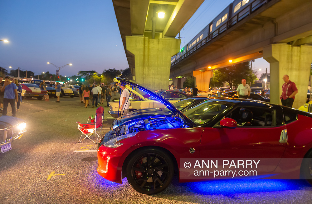 Bellmore, NY, USA. August 24, 2018. Red 2014 Nissan 370Z, with open hood showing engine area lit blue, is parked under elevated tracks that westbound LIRR train is traveling on, during Bellmore Friday Night Car Show.