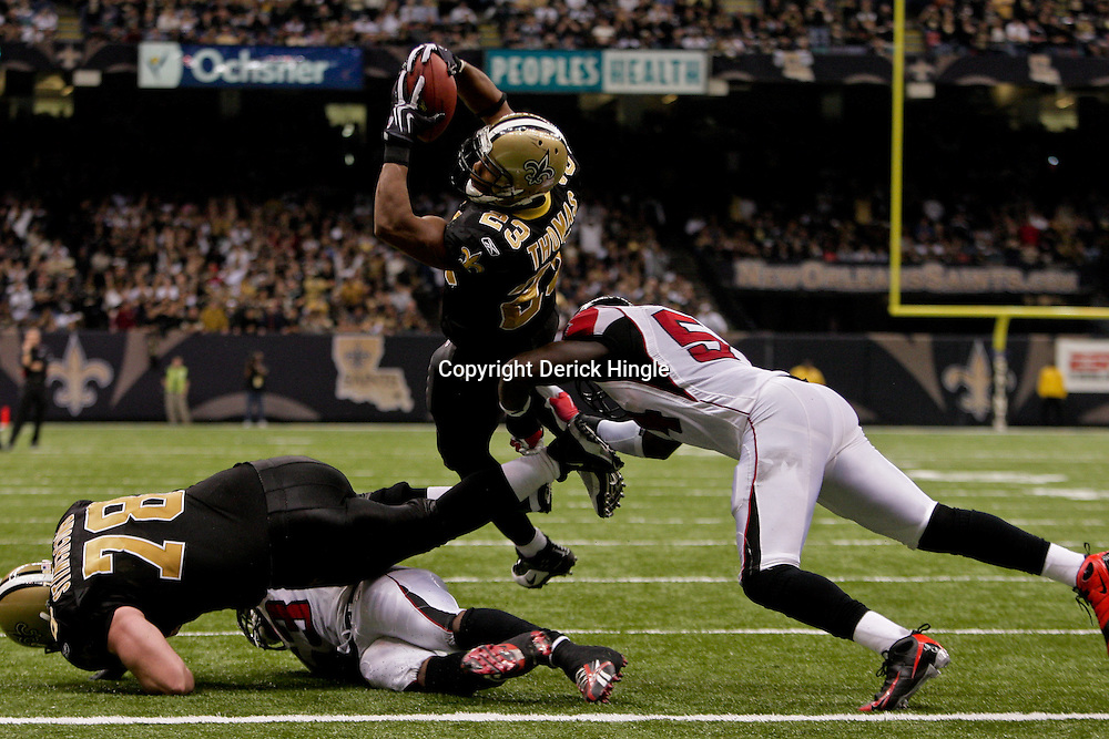 2009 November 02: New Orleans Saints running back Pierre Thomas (23) leaps over Atlanta Falcons linebacker Stephen Nicholas (54) for a touchdown during a 35-27 win by the Saints over the Falcons at the Louisiana Superdome in New Orleans, Louisiana.