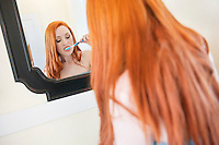 Young woman brushing teeth bathroom