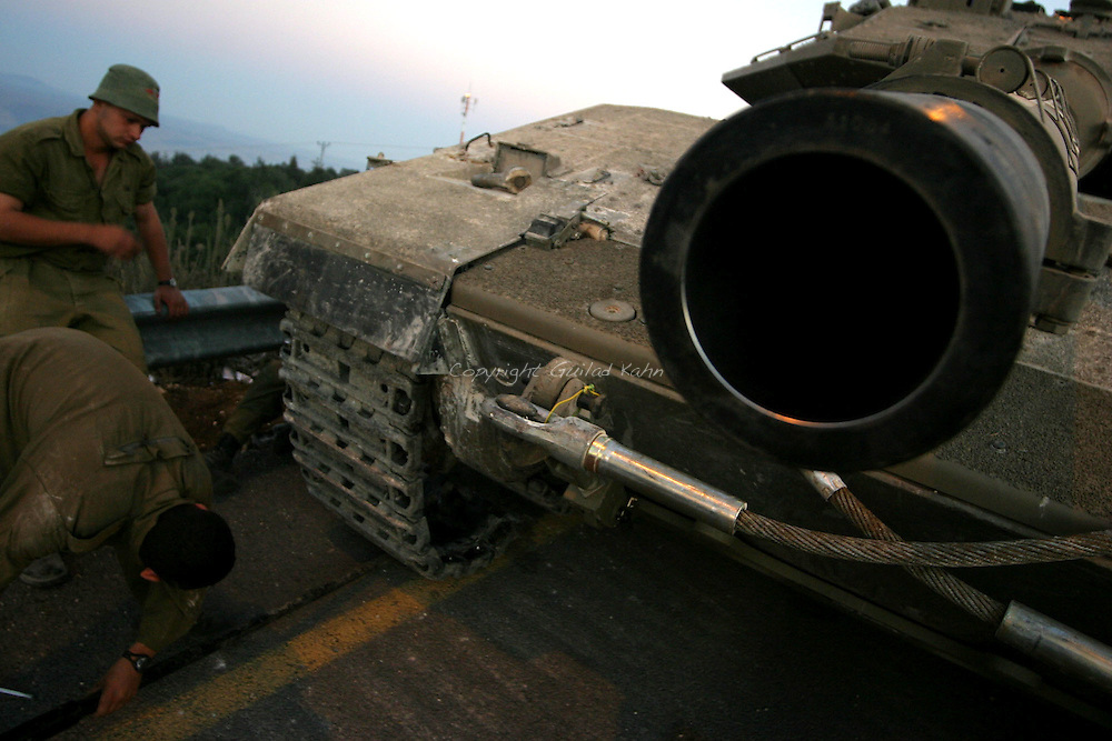 IDF soldiers make adjustments on a tank on the border while waiting for their next mission in southern Lebanon on Wednesday August 2st 2006..