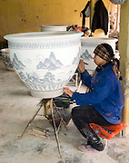 female artist painting large pottery vase; pottery factory; winter clothes; north Vietnam