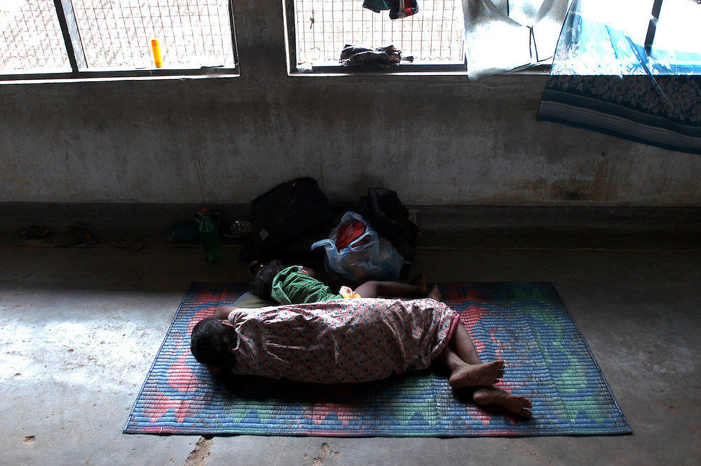 A woman and her child sleep in one of the buildings of the Koddaimunai Junior School after her home was destroyed by the December 26, 2004 Tsunami that struck S.E. Asia following a 9.0 earthquake in the Indian Ocean..Batticaloa, Sri Lanka. 11/01/2005.Photo © J.B. Russell