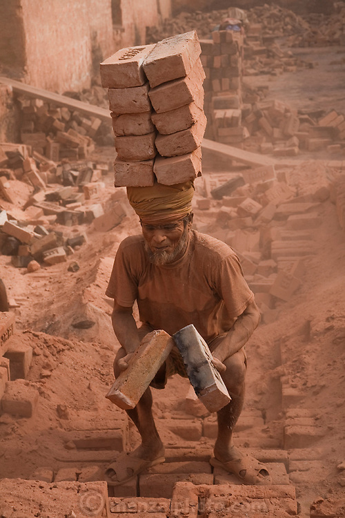 A brick hauler loads a stack of bricks at the JRB brick factory near Sonargaon, outside Dhaka, Bangladesh. The heavy clay soils along the river near the market town of Sonargaon are well suited for making bricks. At the JRB brick factory, workers of all ages move raw bricks from long, stacked rows, where they first dry in the sun, to the smoky coal-fired kilns. After being fired, the bricks turn red. A foreman keeps tally, handing the workers colored plastic tokens corresponding to the number of bricks they carry past him. They cash in the chips at the end of each shift, taking home the equivalent of $2 to $4 (USD) a day.