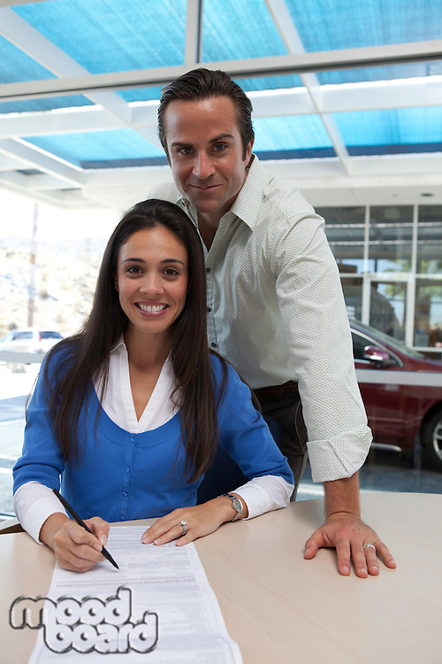 Portrait of woman signing car contract with husband standing behind