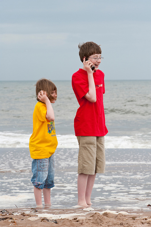 "Children on a beach with cell phone and ""shell phone"", Scotland"
