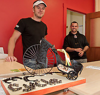 "Miles Chase and CJ Best of MC Cycle admire their ""high wheeled"" shoe created by Sue and Randy Bullerwell of All My Life Jewelers during the Downtown Still Has Sole event ongoing through Thursday.  (Karen Bobotas/for the Laconia Daily Sun)"