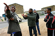 Youngsters on the streets of the impoverished neighbourhood of Heideveld, Cape Town, RSA. Here in front of their house. (Marvin in the middle and former gangster Fuad on the right). Being in so close contact with members of gangs and criminal activity, youngsters are those who are most tempted to join a gang, which most of the time is also probably composed by friends and others living in the community. Making errands or favours to gang members is also common to the younger kids (?wannabes?) in these areas which are lured by the apparently easy gains deriving from the activity.  With extremely high rates of unemployment, poor resources and too little authority control, ghettos as Heideveld are the best places for gangs to grow in activity and businesses. Targeting mostly young people from their area to carry on the ?dirty job?, gangs in the Western Cape, and South Africa are an endemic problem in continuous increase in the years after the radical apartheid governmental system. ?Coloured? communities have lost almost all their help from a government that now is concentrated on empowering black communities instead. Segregated into ghettos and without state grants or development activities, people in these communities are sometimes forced to join a gang or dealing drugs also to provide for their own family. Young gangster are also used for the worst crimes by the fact that, being still under 18 years old, they would face shorter sentences if caught. Drug abuse between kids as young as 12 is not uncommon, especially crystal meth, mandrax and marijuana.
