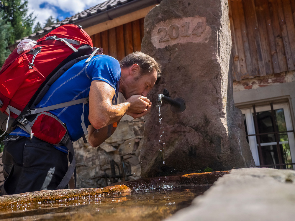 Male hiker drinking water from source in Simonswald, Baden-Wuerttemerg, Germany