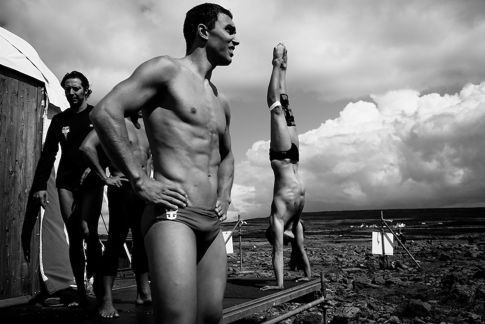 High divers (left to right) Cyrille Oumedjkane, Michal Navratil, and Artem Silchenko stretch and warm up ahead of their dives. The Red Bull Cliff Diving World Series 2012, Inis Mor, Ireland. 04 August 2012
