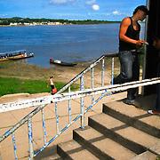 FRONTERA COLOMBO-VENEZOLANA<br /> (Copyright © Aaron Sosa)<br /> Puesto fronterizo del Ejercito Venezolano. Al otro lado del Rio Orinoco se aprecia el poblado de Casuarito, Colombia.<br /> En la grafica se aprecia un joven cobrando el pasaje a los pasajeros de la lancha.<br /> Puerto Ayacucho, Estado Amazonas, Venezuela 2008
