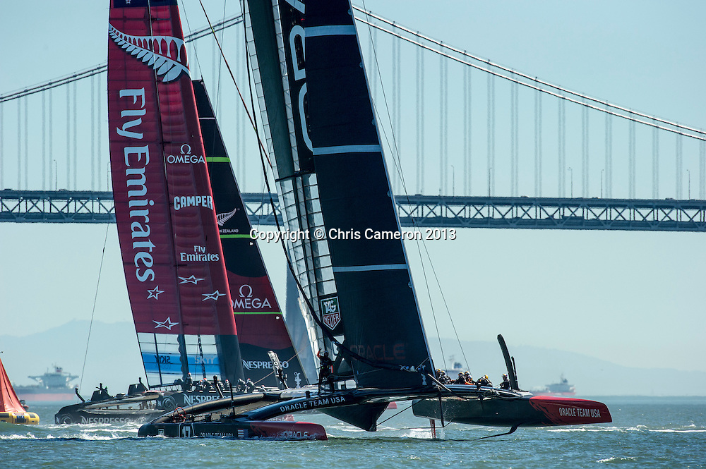 Oracle Team USA round the bottom mark ahead of Emirates Team New Zealand in race 16 on day 13 of America's Cup 34. 23/9/2013