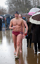 © Licensed to London News Pictures. 25/12/2012. London, UK. Members of the Serpentine Swimming Club walk through pouring rain to get dressed after finishing the Serpentine Swimming Club's annual Christmas morning 'Peter Pan Cup' race in Hyde Park, London, today (25/12/12).   The race, which takes place every Christmas Day on the Serpentine River, takes its name from from the novel by J.M.Barrie after the author presented the first Peter Pan Cup in 1904. Photo credit: Matt Cetti-Roberts/LNP