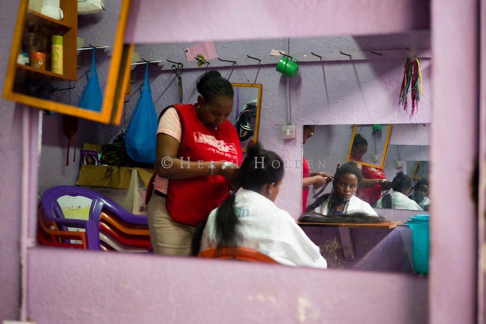 The Kenyatta Market is known as the hair capital, young Kenyans flock here to update their hair styles. A young women simply known as Mary receives fresh braids in one of the many market salons in Nairobi, Kenya on Sunday 15th of September.