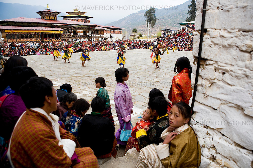 Local people watch masked drummers dance at the Paro  festival at Rinpung dzong, Paro...Commonly described as the last Himalayan Shangrila, Bhutan is a country of unique serenity, harmony, and beauty. Nestled between India, China, and Tibet, this independent country whose name translates as 'the Land of the Thunder Dragon' has for the past 300 years  proactively followed a policy of isolation and cultural protection. Travel in and out of the country is strictly regulated, and the impact of outside influences on the local culture is carefully monitored. Spirituality is an important aspect of Bhutanese culture, with Buddhism being interlinked with everyday life. Gross National Happiness (GNH), as opposed to GNP/GDP, forms the cornerstone of its development strategy which focuses on a holistic development strategy that complements its cultural and Buddhist spiritual values.