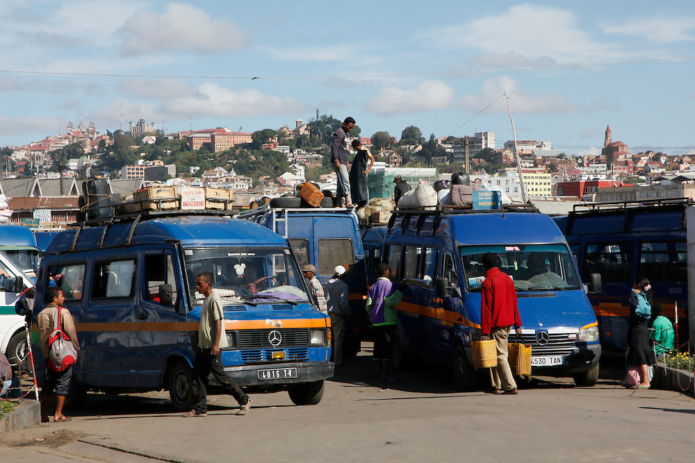 Taxi 'brousse'  being loaded at Andravoahangy market with view of central Tana on the hills in the background. Street scenes and daily life in Antananarivo the capital of Madagascar. ..Photo: Zute Lightfoot