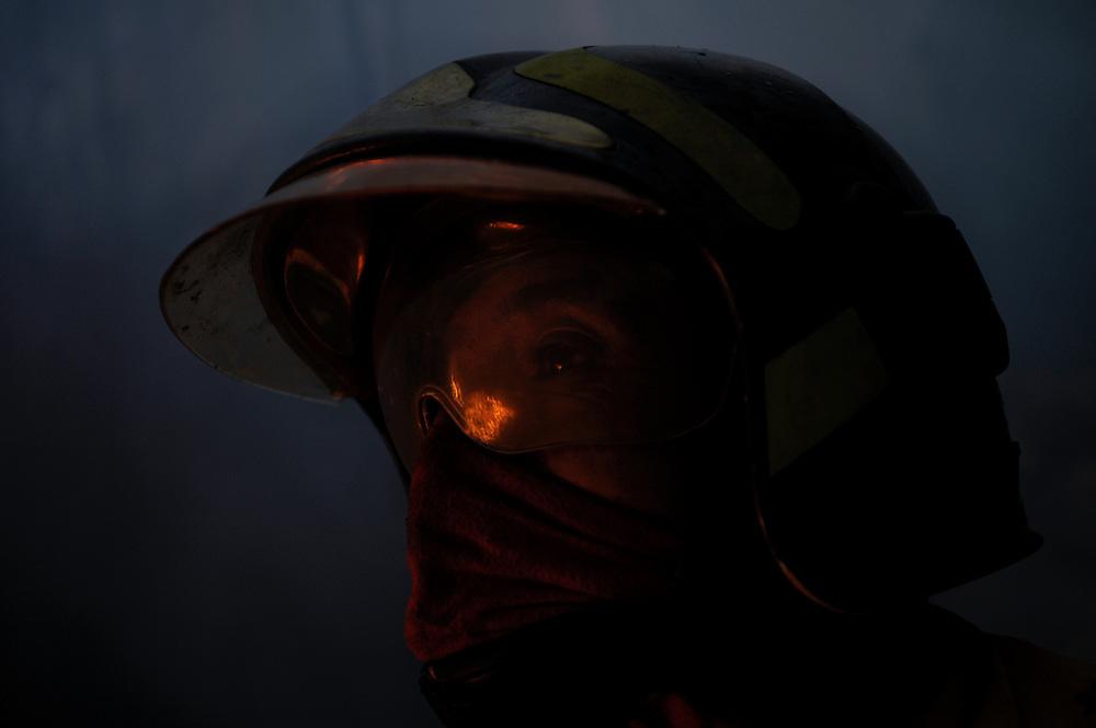 Un bombero mira un incendio forestal crecer fuera de su alcance. Durante una sequía de dos meses, aproximadamente 2565 incendios forestales, (muchos presuntamente provocados) quemaron 3796 hectareas de bosques, algunas casas y muchos animales silvestres en las laderas boscosas que rodean Quito, la capital del Ecaudor.   Ningún humano murió, pero tomaran décadas antes de que las áreas afectadas se recuperen.