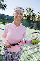 Senior woman on tennis court, portrait
