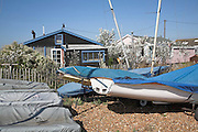 Bungalow chalets and sailing dinghies. Small fishing and sailing hamlet of Felixstowe Ferry at the mouth of the River Deben, Suffolk, England