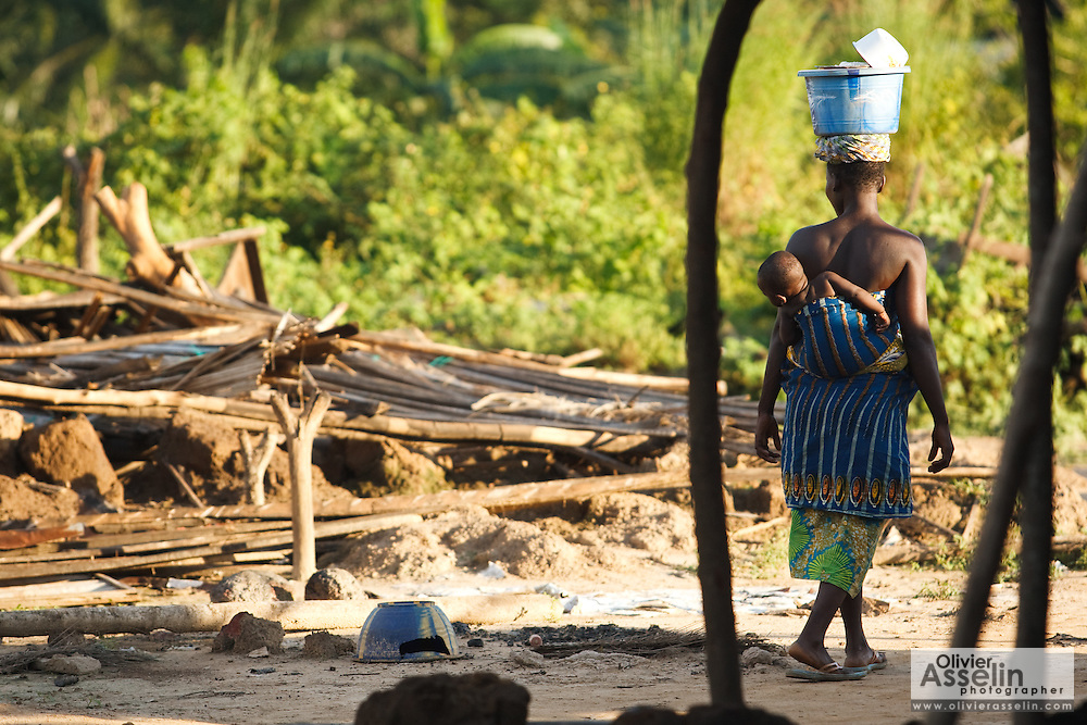 A woman carrying her child looks back as she walks past a destroyed home in the village of Kpoto, Benin on Tuesday October 26, 2010.  Waters have receded in Kpoto, but most of the village was literally flattened by floods that have hit Benin over the past few weeks..