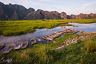 A row of empty fishing boats line the shore in Van Long Wetland Nature Reserve, Gia Vien District, Ninh Binh Province, Vietnam, Southeast Asia