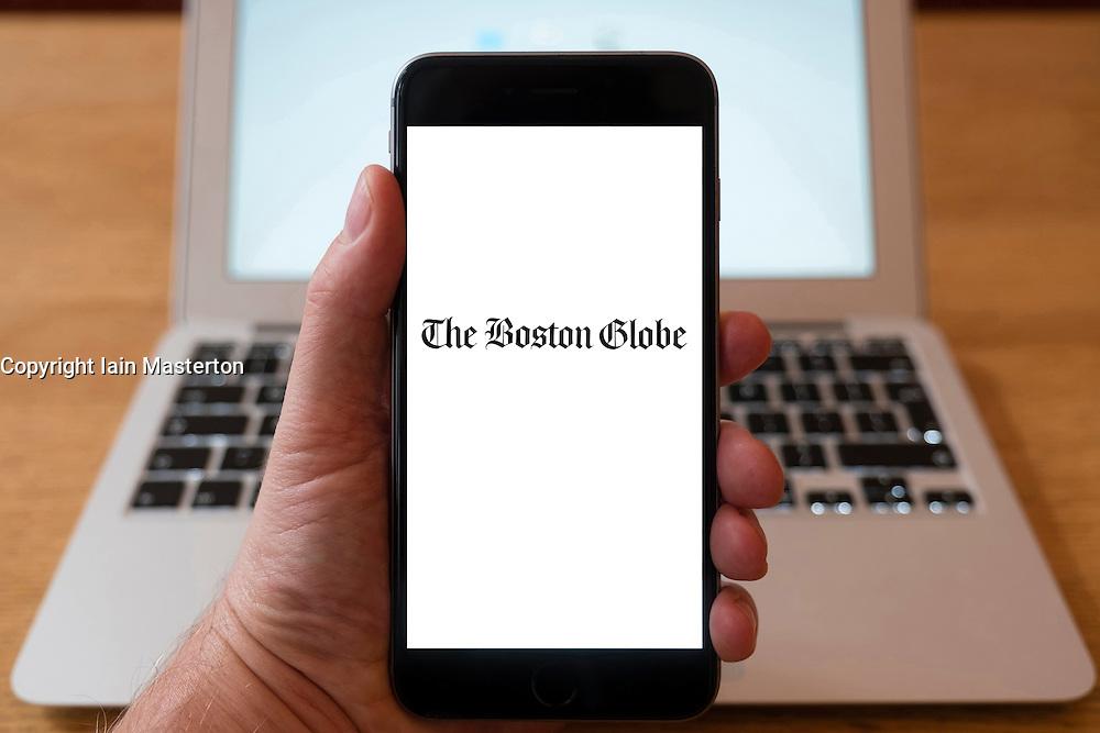 Using iPhone smartphone to display logo of The Boston Globe newspaper in USA