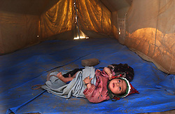 ZHARE DASHT,AFGHANISTAN - SEPT. 4: A Pashtun Afghan baby who was living in a camp for displaced people around Spin Boldak, near the border of Pakistan and southern Afghanistan, sits in an empty tent after her family was relocated to Zhare Dasht by the UNHCR September 4, 2002.  As an estimated 1.6 million Afghan refugees return to Afghanistan,  ethnic Pashtuns from northern Afghanistan are seeking safety in   camps in the south. Numbering up to 120,000,  Pashtuns are fleeing the Tajik- and Uzbek-dominated cities of the north out of fear and prefer to live in the dismal camps like Zhare Dasht which is set in the middle of a desert surrounded by mines about 30 kilometers west of Kandahar. (Photo by Ami Vitale/Getty Images)