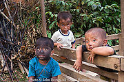 Three boys with dirty faces are gathered on a wooden hauling cart while living n poverty as slash and burn subsistence farm children near Vang Vieng, Laos.