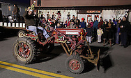 Pine Bush, New York  - A man driving a Farmall tractor decorated for the holiday waves to the crowd during the parade down Main Street at the Community Country Christmas 2011 celebration on Dec. 3, 2011.