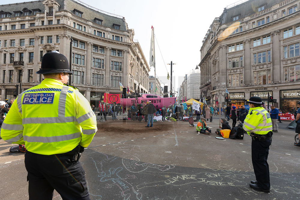 © Licensed to London News Pictures. 17/04/2019. Police officers watch as environmental activists from the Extinction Rebellion movement continute to protest and block the road at Oxford Circus as part of a series of direct actions taking place across the capital. The protests demand urgent action from governments on climate change. Photo credit: Vickie Flores/LNP