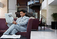 Business man reading newspaper smiling