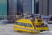 Crowded water taxi head off for Manhattan with Pier 17 in the background.