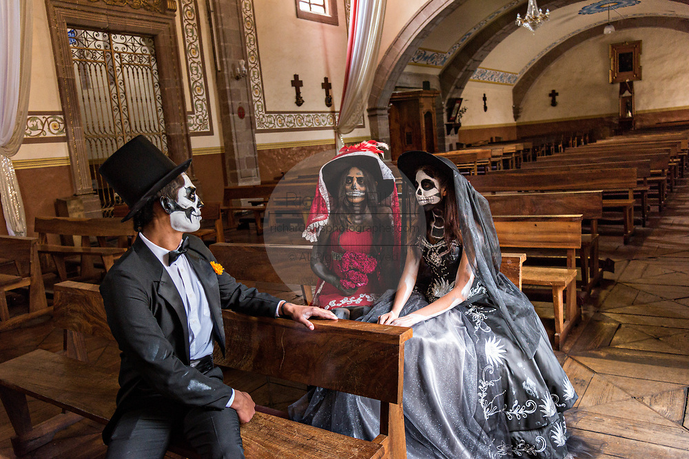 Mexican teens dressed in La Calavera Catrina and Dapper Skeleton costumes sit in the Templo del Sagrario during the Day of the Dead or Día de Muertos festival October 31, 2017 in Patzcuaro, Michoacan, Mexico. The festival has been celebrated since the Aztec empire celebrates ancestors and deceased loved ones.