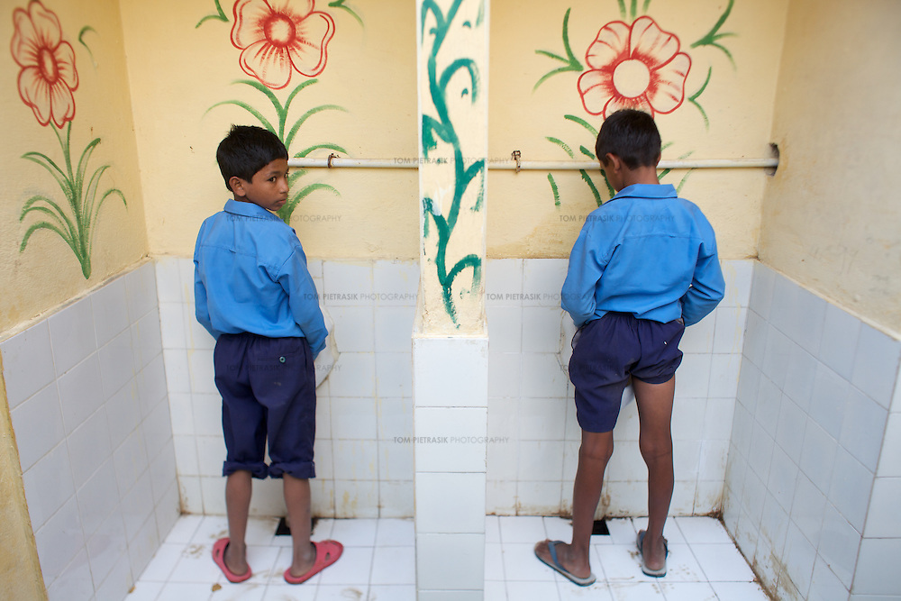 Two pupils at Niyamatpur Khurd primary school use the boys urinals. The school handwashing area and toilet are adorned with colourful paintings and are an example of the kind of attractive facitilty encouraged by UNICEF...UNICEF and the Uttar Pradesh Government, have identified 36 model Gram Panchayats (local-level village administration) in Mirzapur District. The promotion of good sanitation and hygiene practices in these Gram Panchayats allows them to serve as examples for the remaining areas of the district to emulate. The promotion of hygiene and sanitation includes the construction and painting of school toilet blocks, the construction of individual toilets in households, the digging of garbage pits, recycling waste water and encouraging personal hygiene awareness. ..Only 32 percent of those living in Uttar Pradesh, India's largest state, have access to a toilet. Uttar Pradesh faces many challenges in it's efforts to address this deficiency. UNICEF supports the Uttar Pradesh government's sanitation and hygiene project at both the state and district levels. UNICEF is working to increase the capacity of all of those involved in the sanitation and hygiene project from state-level administrators through to Panchayati Raj (local-level administration) officers and influential individuals, including teachers, who live among rural communities. UNICEF has prioritised the need to communicate the importance of good sanitation and hygiene practice to these communities. The Uttar Pradesh government and UNICEF have focussed their campaign on eight districts (including Mirzapur) with the intention that these serve as models for the remaining 62 districts of the state. UNICEF have identified areas of shortcoming within the government program and proposed solutions. These solutions include the proper training of masons, the provision of rural pans (toilet bowls which require less water per flush) and the identifying of local motivators who champion the program on the ground. Th