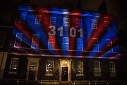 London, UK. 31 January, 2020. Numbers spelling the date, 31st January, appear on a Brexit countdown clock projected against a background of red, white and blue lighting onto 10 Downing Street to count down to the moment when the UK leaves the European Union.