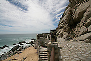 Stairway, a beach entrance to El Farallon restaurant at Capella Pedregal in Cabo San Lucas, Mexico. The soft white blue sky makes a dramatic contrast to the harsh stone mountain.
