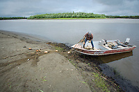 Henry Spein pulls a set net for subsistence fishing into his skiff near Kwethluk, Alaska. ..With both ends anchored, the top of the set net is held by floats while the net sinks to the bottom. From his skiff Spein will pull fish from the nets later in the day.