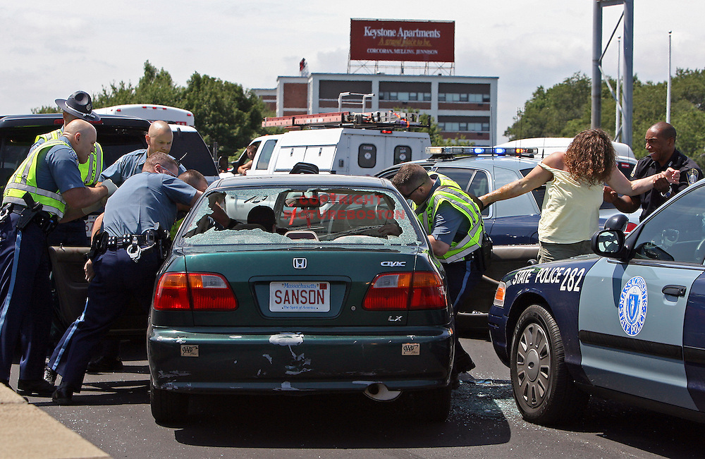 Police free the victim, whose hand is tangled in the seat belt, as they enter the car.