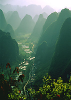 A small dirt road runs down through valley of stunning limestone karsts alongside flooded rice paddies, Yangshuo, China.