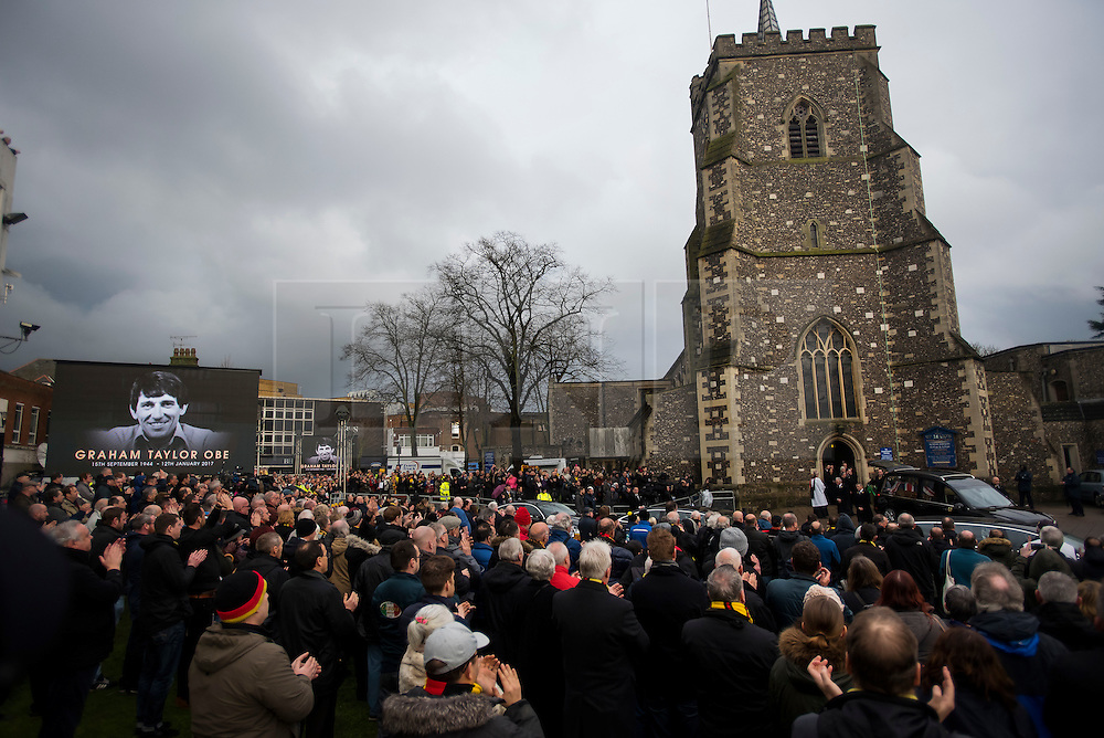 © Licensed to London News Pictures. 01/02/2017. Watford, UK. Mourners and football fans watch the coffin leave the church at the funeral of former England football team manager Graham Taylor at St Mary's Church in Watford, Hertfordshire. The former England, Watford and Aston Villa manager,  who later went on to be chairman of Watford Football Club, died at the age of 72 from a suspected heart attack. Photo credit: Ben Cawthra/LNP