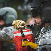 US Army Flight Medic Students wait on line for extraction by rescue hoist