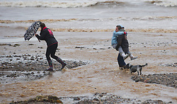 © Licensed to London News Pictures. 25/11/2012..North East England..A family struggle to walk along the beach at Saltburn as it became flooded in parts by run-off rain water following heavy overnight rain that also caused traffic disruption and flooding in parts of Cleveland and North Yorkshire this morning...Photo credit : Ian Forsyth/LNP