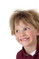 Close-up of blond boy looking sideways over white background