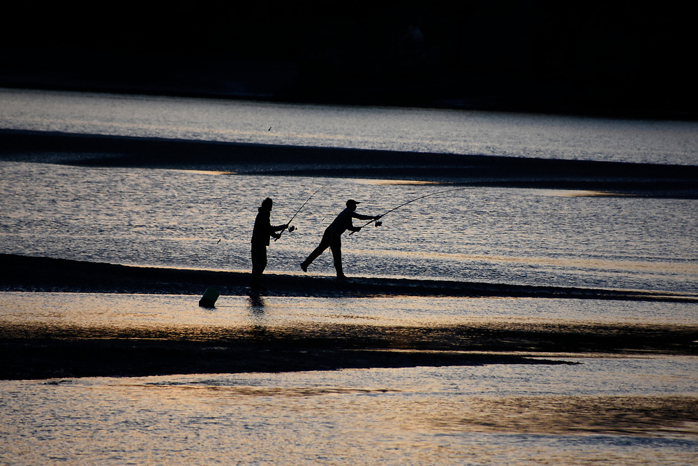 2 men fishing on the sands at sunset in Raglan, NZ